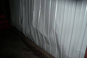 Distress at metal panel wall due to frozen floor heave